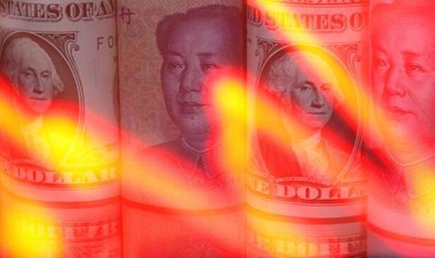 Chinese Yuan and U.S. dollar banknotes are seen behind illuminated