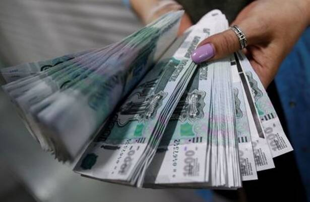 An employee holds 1000 Russian Roubles notes at Goznak printing