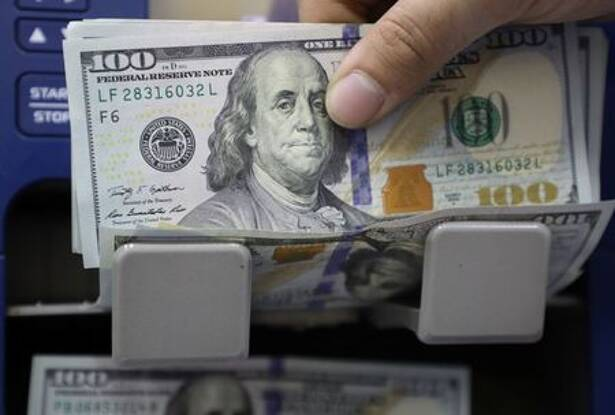 A man counts U.S. dollar banknotes at a currency exchange