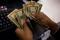 Imagen de archivo de un cajero contando dinero en una tienda de Nueva York, EEUU. 28 noviembre 2013.