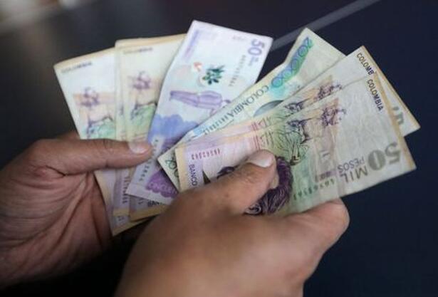 Foto de archivo ilustratia de un hombre con varios billetes de pesos colombianos en una tienda en Bogotá