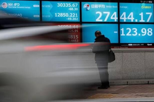 FOTO DE ARCHIVO: Un hombre frente a una pantalla que muestra el índice de acciones Nikkei y los índices bursátiles mundiales en el exterior de una agencia de valores, en Tokio
