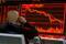 Imagen de archivo de un inversor sentado frente a una pantalla que muestra información bursátil en una correduría en Pekín