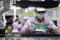 FOTO DE ARCHIVO: Una empleada inspecciona un circuito impreso en una cadena de producción en Wuhan