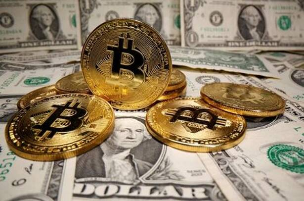 Imagen de archivo ilustrativa de representaciones de la moneda virtual bitcóin puestas sobre billetes de dólares estadounidenses