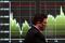 Imagen de archivo de un hombre con mascarilla caminando frente a una pantalla que muestra un gráfico de los movimientos recientes del índice Nikkei afuera de una correduría en Tokio
