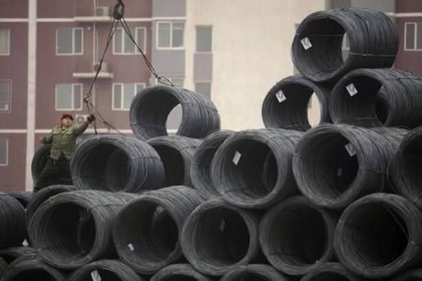 Imagen de archivo. Un obrero trabaja en bobinas de alambre de acero en un mercado mayorista de acero en Pekín