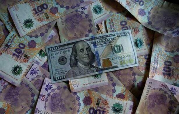 Un billete de cien dólares estadounidenses reposa sobre billetes devaluados de cien pesos de Argentina en esta ilustración fotográfica