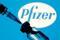 Impfstoff-Ampulle und Spritze vor dem Pfizer-Logo, 11. Januar 2021.